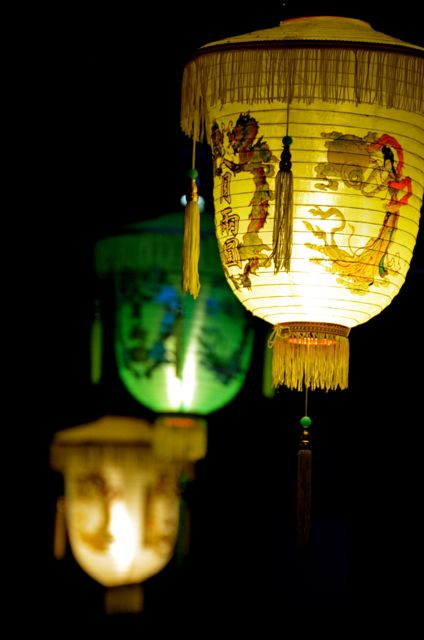 One green and two yellow lanterns glow in Hoi An, Vietnam.