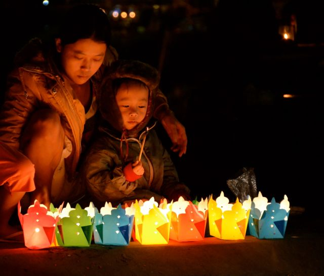 Mother and child with luminaries in Hoi An Vietnam