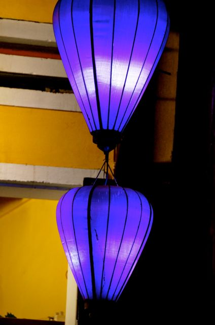 Two purple lanterns are illuminated outside a business in Hoi An, Vietnam.