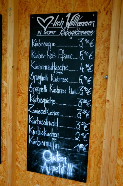 The chalkboard menu at the Ludwigsburg Pumpkin Fest displays food items in German. There's everything from pumpkin soup and pumpkin strudel to pumpkin spaghetti. Prices in Euro are also included.