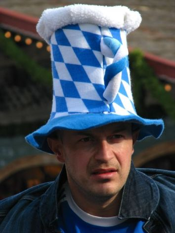 Man in Bavarian beer mug hat at Oktoberfest