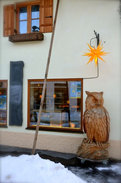 A yellow Christmas star and a large, wooden carved owl in Oberammergau, a town in Germany's Bavaria region.