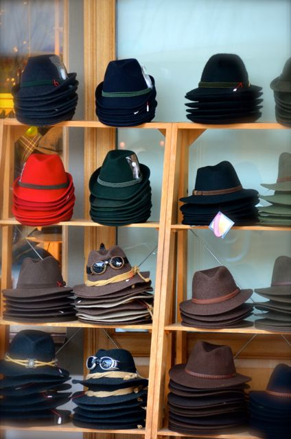 Red, green, blue, grey, and brown winter woolen hats sit on an outdoor  display outside a shop in Oberammergau, Germany.