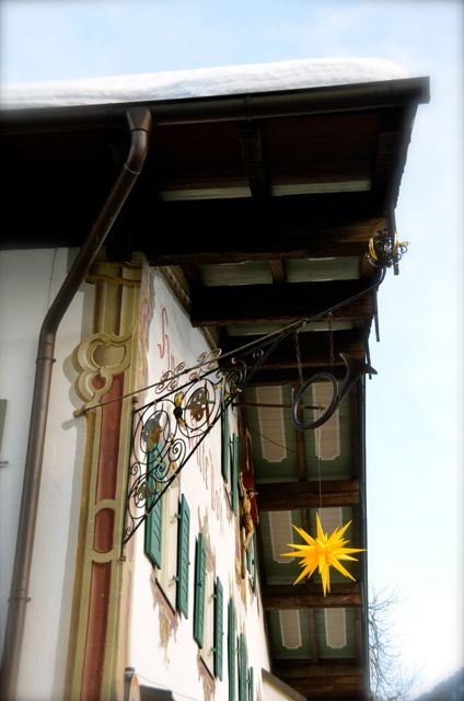A yellow star decoration hangs on a chalet-style building covered in snow in Oberammergau, Germany.