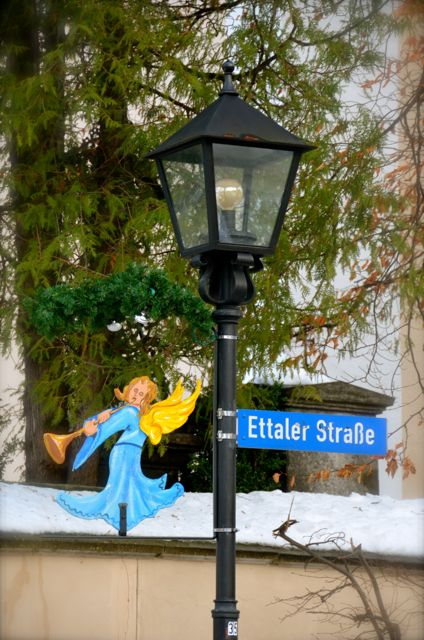 An Oberammergau, Germany street sign is decorated during Christmas with an angel playing a horn.