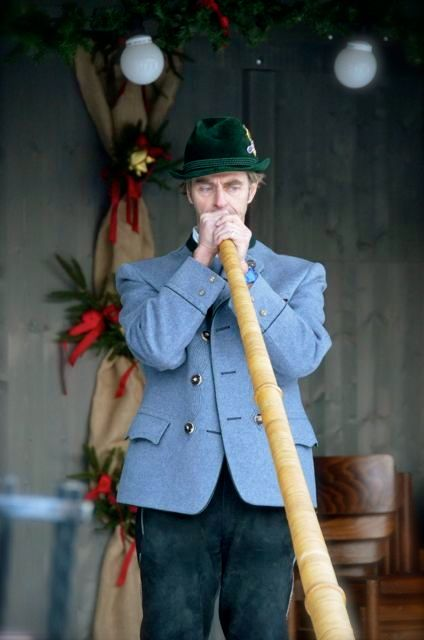A man plays an Alphorn in Bavaria, Germany.