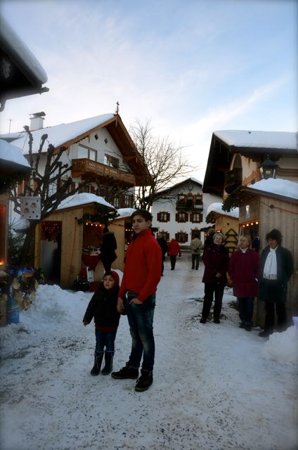 People stand outside a Christmas market in Oberammergau, Germany. There is snow on the ground.