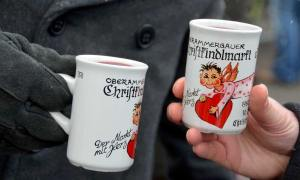 "Two male hands, holding white ""Christkindlmarkt"" mugs filled with Gluhwein (mulled wine) at the Oberammergau, Germany Christkindlmarkt."