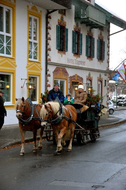 A horse-drawn sleigh carries passengers past frescoed homes in Oberammergau, Germany, on the occasion of St. Nicholas Day.