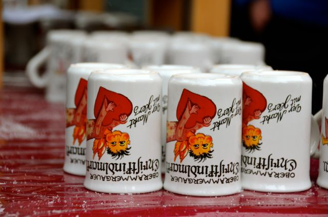 White Christkindlmarkt mugs are stored upside down on a red table at a German Christmas market.