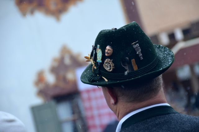 A man wears a traditional green Bavarian hat decorated with pins.