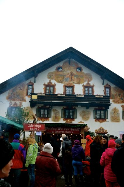 A German winter holiday market is overlooked by a traditionally painted house on a grey day.