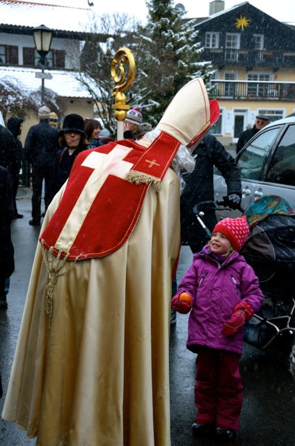 A man, dressed as St. Nicholas, hands a child an orange at a German Christkindlmarkt in Bavaria.