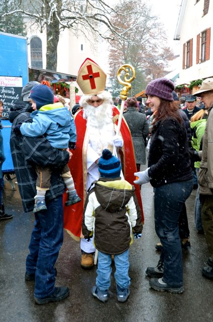Families meet a man dressed as St. Nicholas at an outdoor holiday market in Germany.