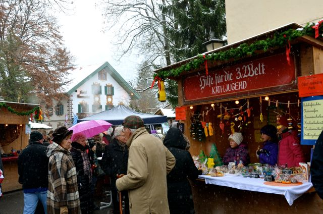 People socialize at an outdoor holiday market in Oberammergau, Germany.