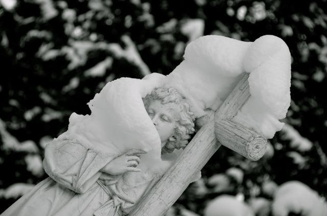 Angel headstone draped in snow in germany