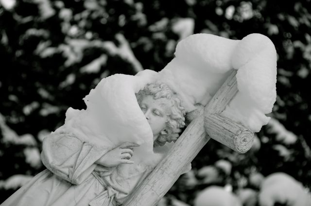 Angel headstone draped in snow in germany