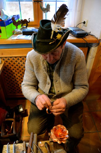 A coppersmith makes a copper bracelet in Oberammergau, Germany.