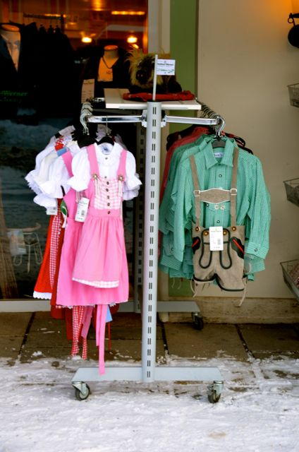 Traditional Bavarian clothes hang outside on clothing racks in Oberammergau, Germany.
