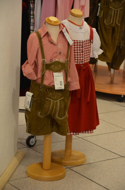 Children's traditional Bavarian clothes for sale in an Oberammergau shop: Lederhosen and a red and white checked shirt (left) and a red, checkered Dirndl (right).