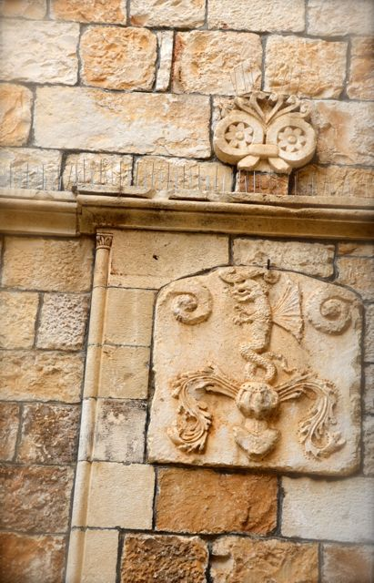 A coat of arm on a stone home in Trogir, Croatia depicts a winged dragon.