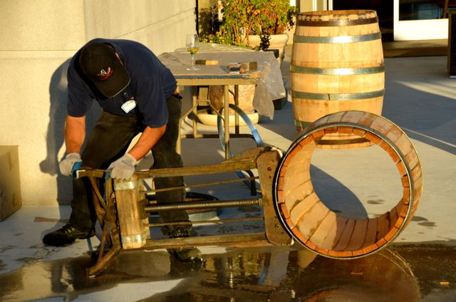 A man crafts a wooden wine barrel in California.
