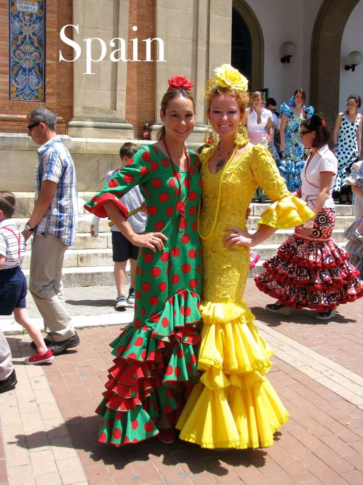 Two women dressed in feria dresses outside of Sevilla, Spain.