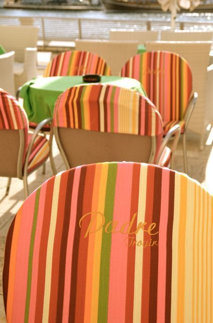 Bright, pastel-colored striped chairs at a cafe in Trogir, Croatia.