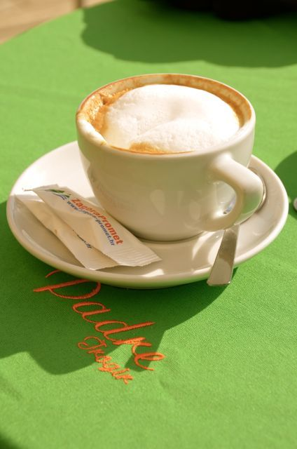 A cup of coffee sits on a green tablecloth in Croatia.