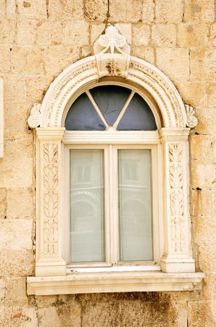 A window frame, which is carved in a decorative fashion, in Trogir, Croatia.