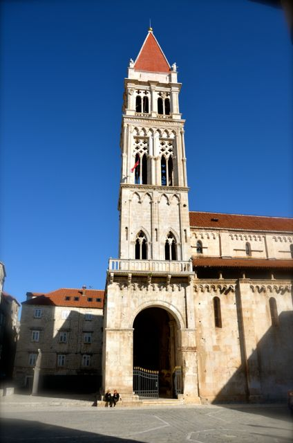Two people sit outside the Cathedral of St. Lawrence in Trogir.