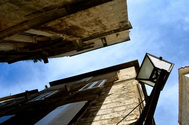 Looking up with Trogir buildings and a blue sky overhead