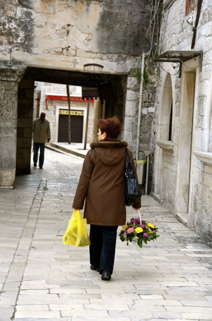 woman carrying flowers in Trogir Croatia old town