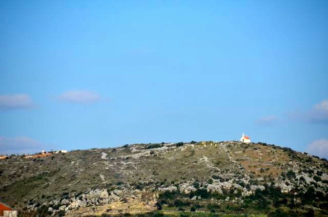 small church on hillside with blue sky overhead in Croatia