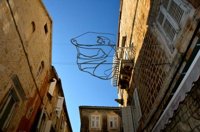 silhouette of Kairos figure above Trogir streets - Croatia