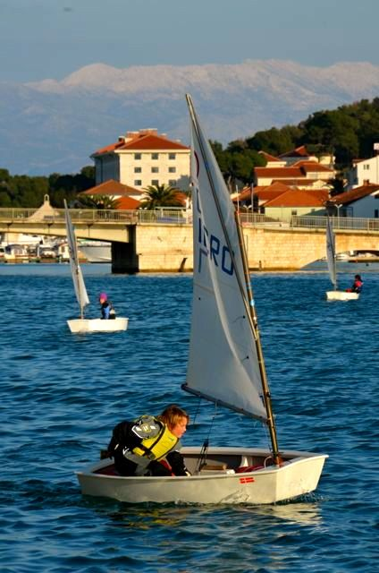 A boy pilots a small sailboat during a lesson in Trogir, Croatia.