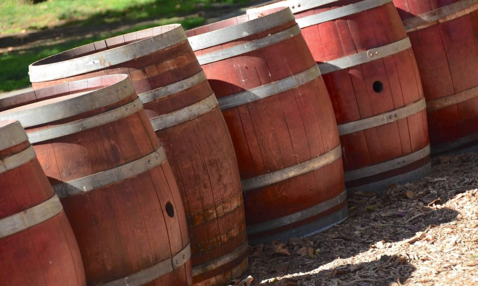Red-toned wine barrels sit outdoors at a Napa Valley winery.