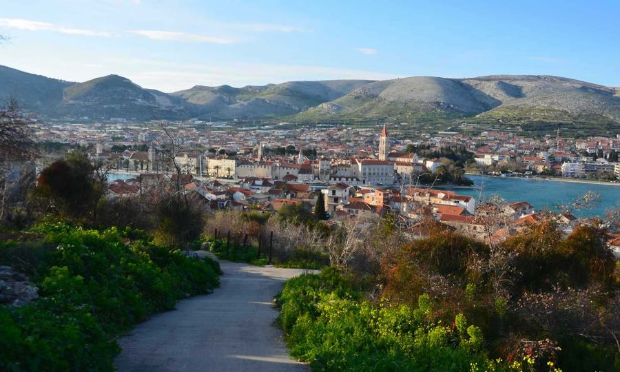 The city of Trogir, Croatia is seen from afar, via a walking path that is surrounded by greenery. You can see mountains in the distance, as well as the Adriatic Sea.
