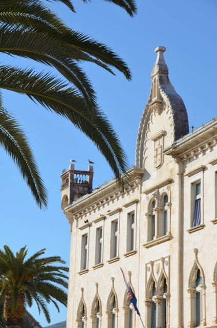 Trogir's Elementary School Building with palm trees in the foreground