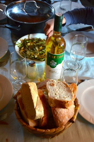 Croatian lunch consisting of wild asparagus and eggs, bread, white wine and chicken and pork