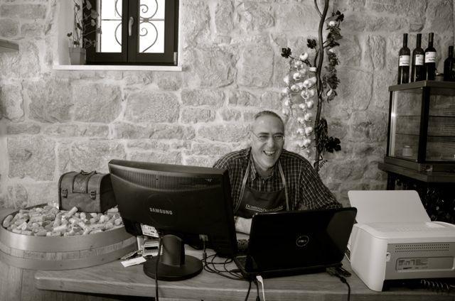 man laughing at desk in Croatian wine bar