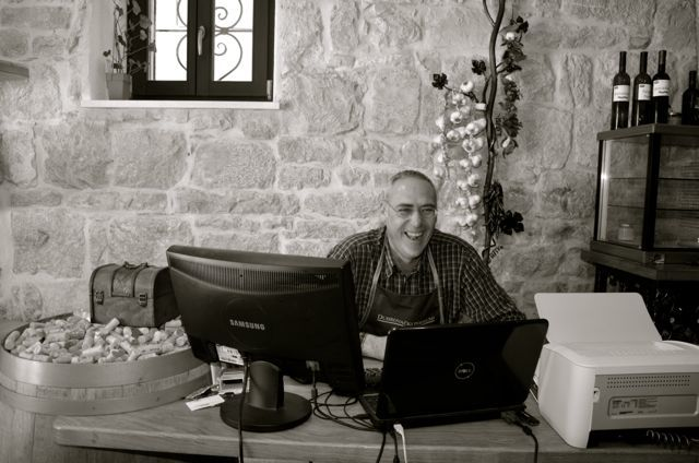 man laughing at desk in Croatian wine bar