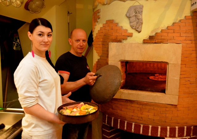 A man and woman stand before a wood-burning oven, preparing to put the peka inside.