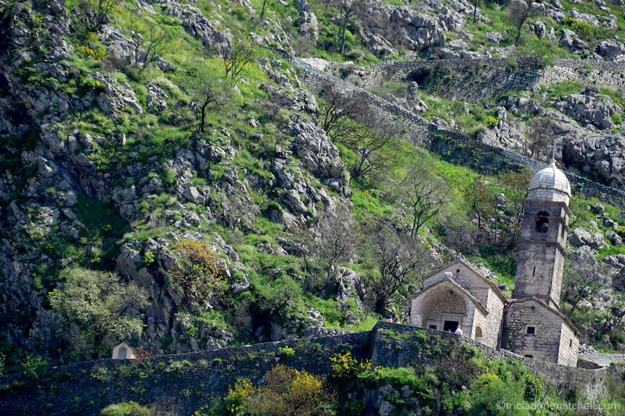 A stone church sits on the rocky hillside overlooking Kotor, Montenegro. it is surrounded by an uphill path, and green foliage.