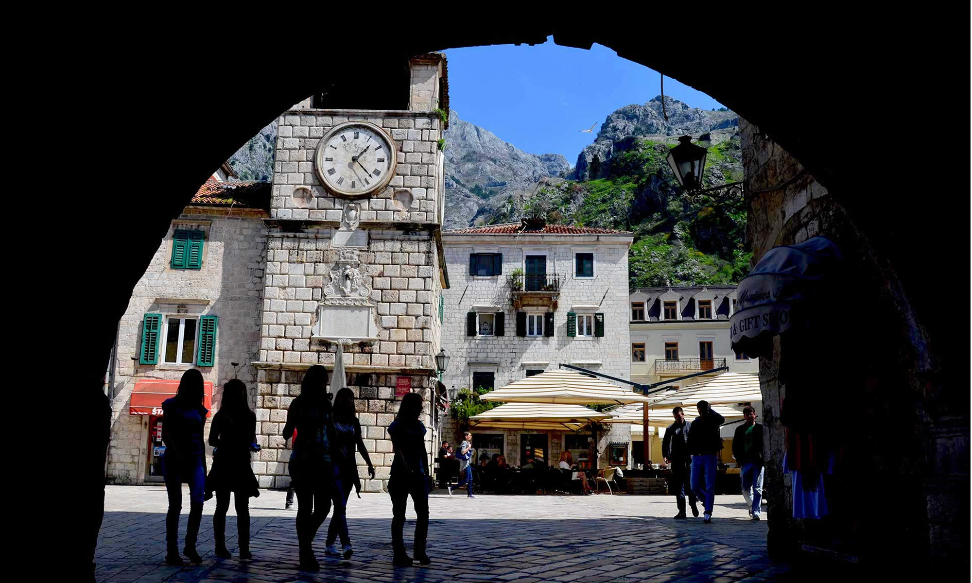 Young women, in silhouetted form, walk through the cobbled streets of the Old Town in Kotor, Montenegro.