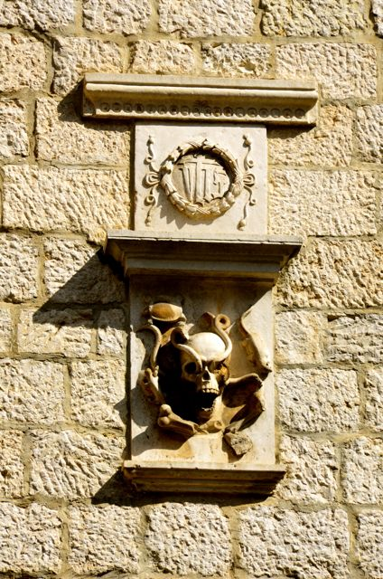 A skull and crest adorn the exterior of a stone building in Kotor, Montenegro.