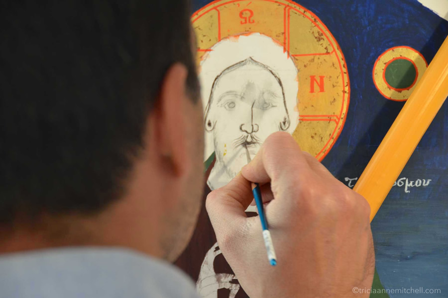 A man paints a Byzantine religious icon with a delicate paintbrush.