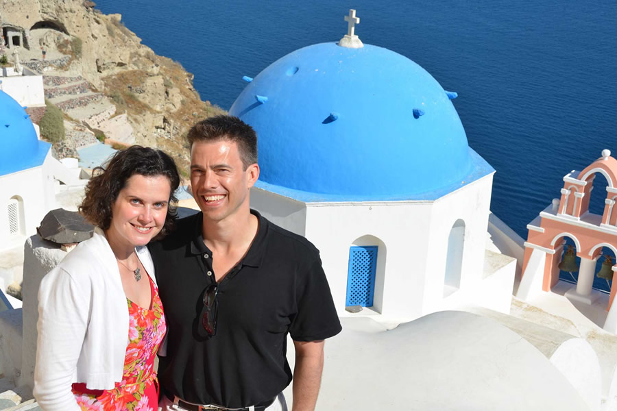 A white building with a blue dome in Oia, Santorini.