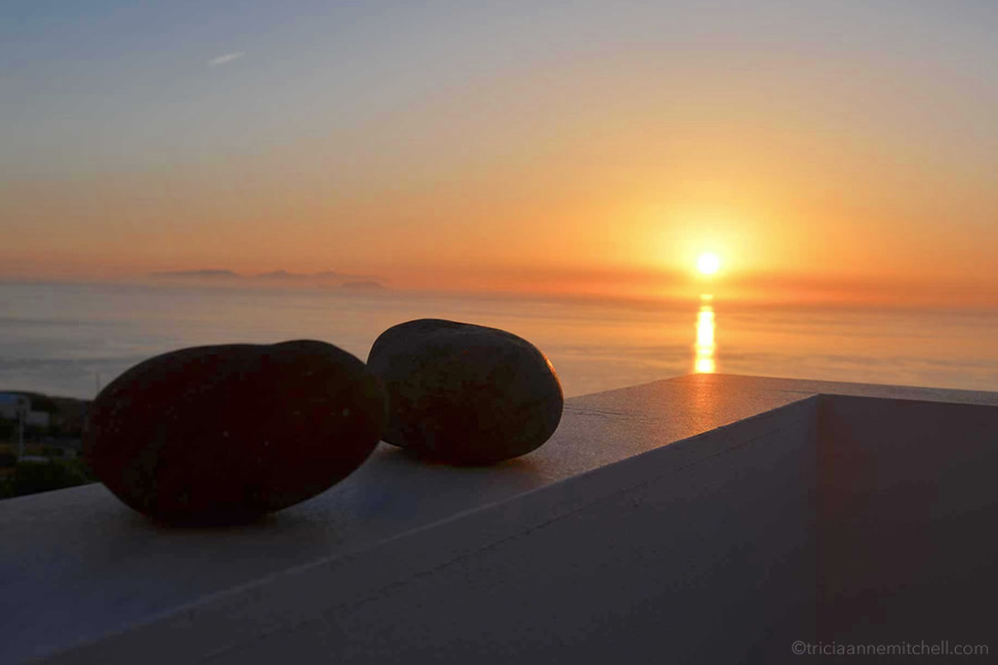 Glimpsed from a balcony, the sun rises over the island of Santorini.