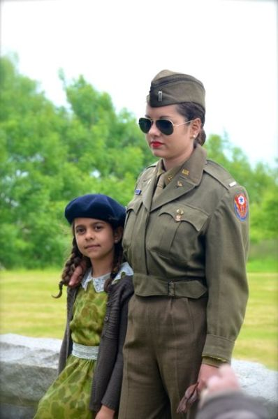 At Normandy anniversary commemorative events, a Woman and girl dressed in 1940s attire